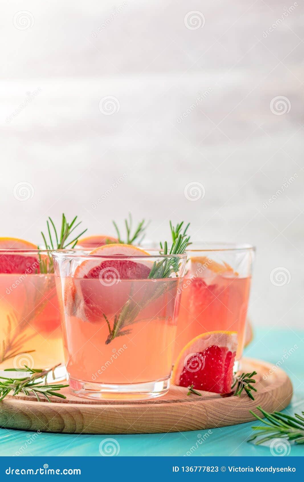 Cocktail alcoólico cor-de-rosa com toranja, gelo e hortelã