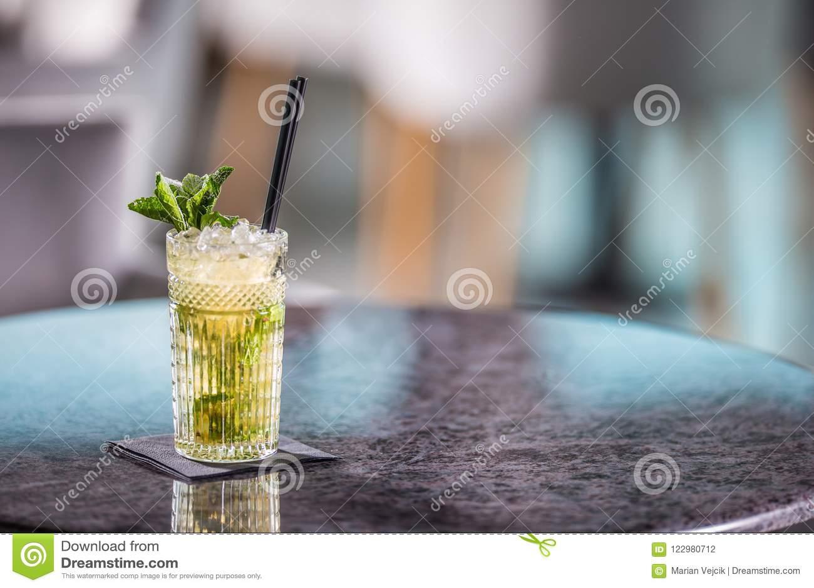 Cocktail alcoólico do verão de Mojito na tabela no restaurante