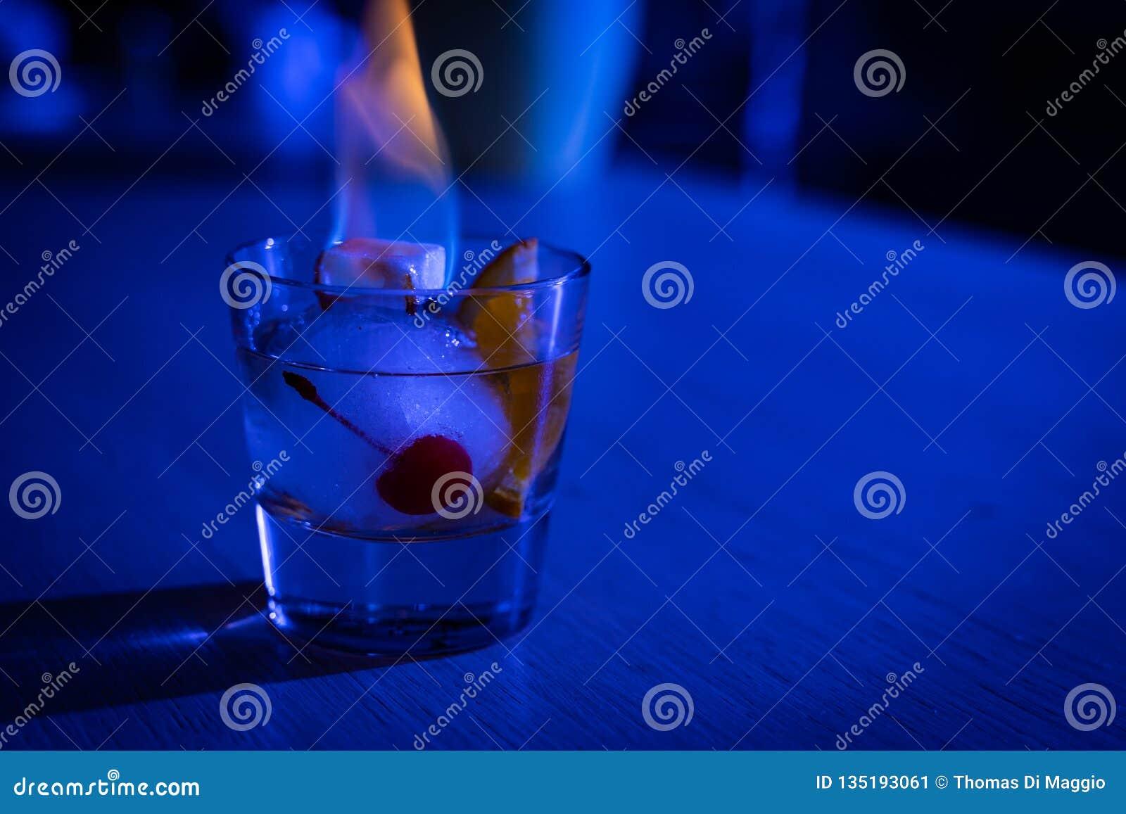 Cocktail antiquato sulla palla di ghiaccio con lo zucchero di combustione