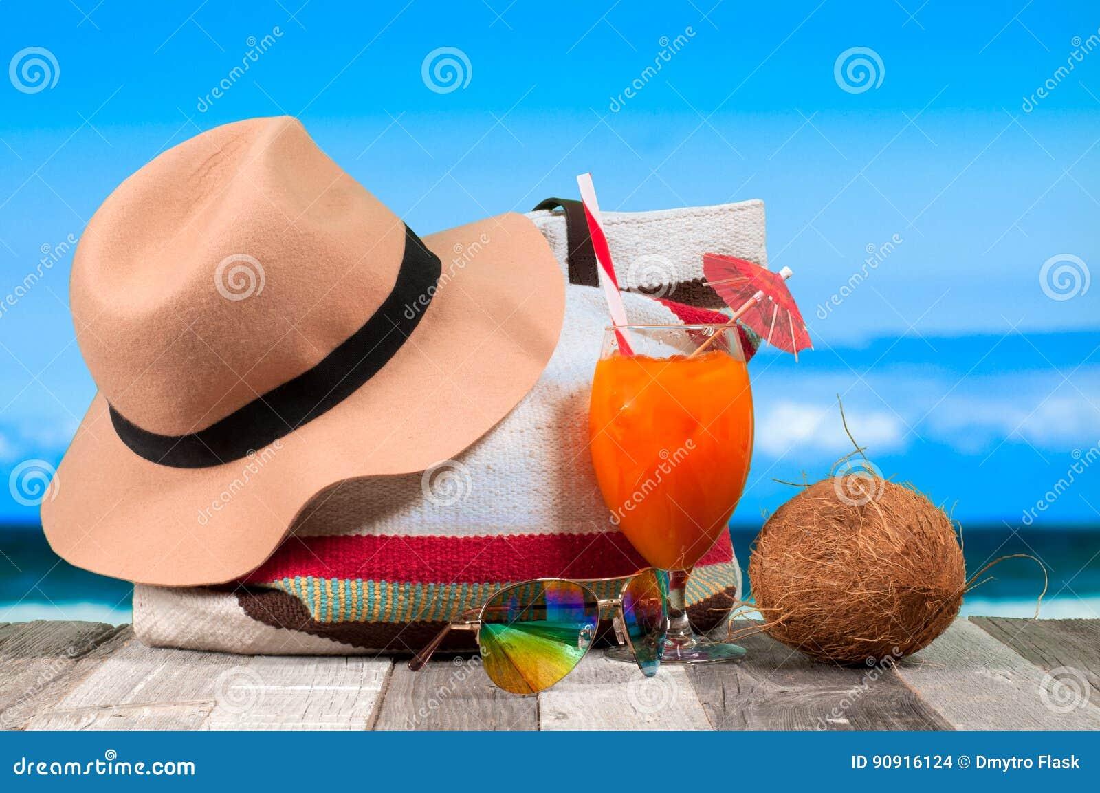 Cocktail arancione di rinfresco sulla tabella della spiaggia Cappello e  borsa di estate 6d30e7bfea5a
