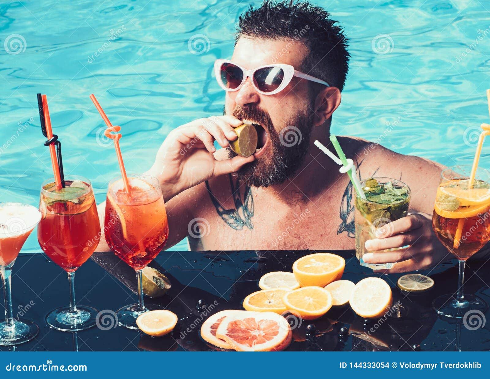 Cocktail avec le fruit à l homme barbu dans la piscine Natation d homme et alcool de boissons Vacances d été à Miami ou les Maldi