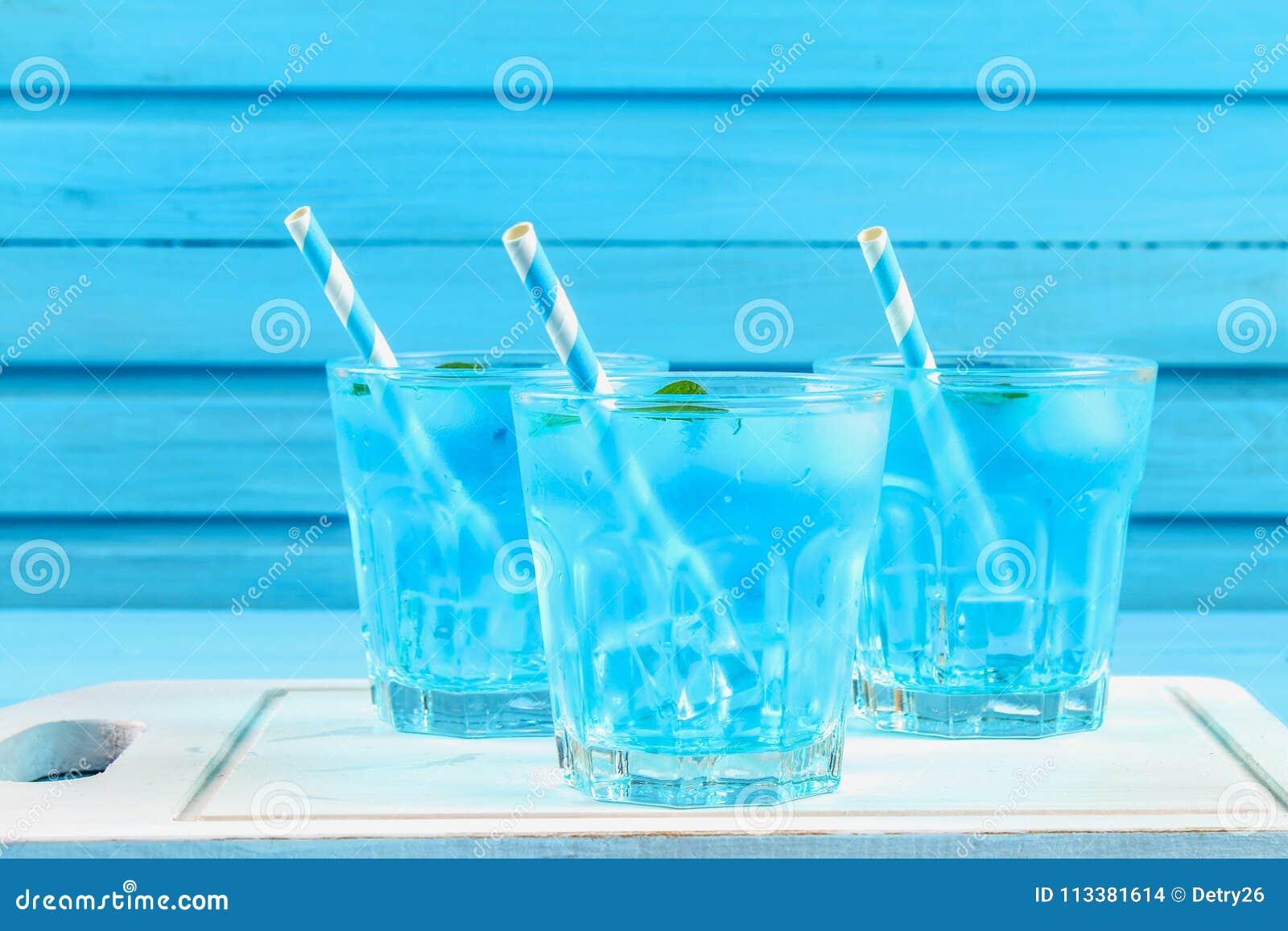 Cocktail azul com gelo e hortelã nos vidros em uma placa de madeira branca em uma tabela azul