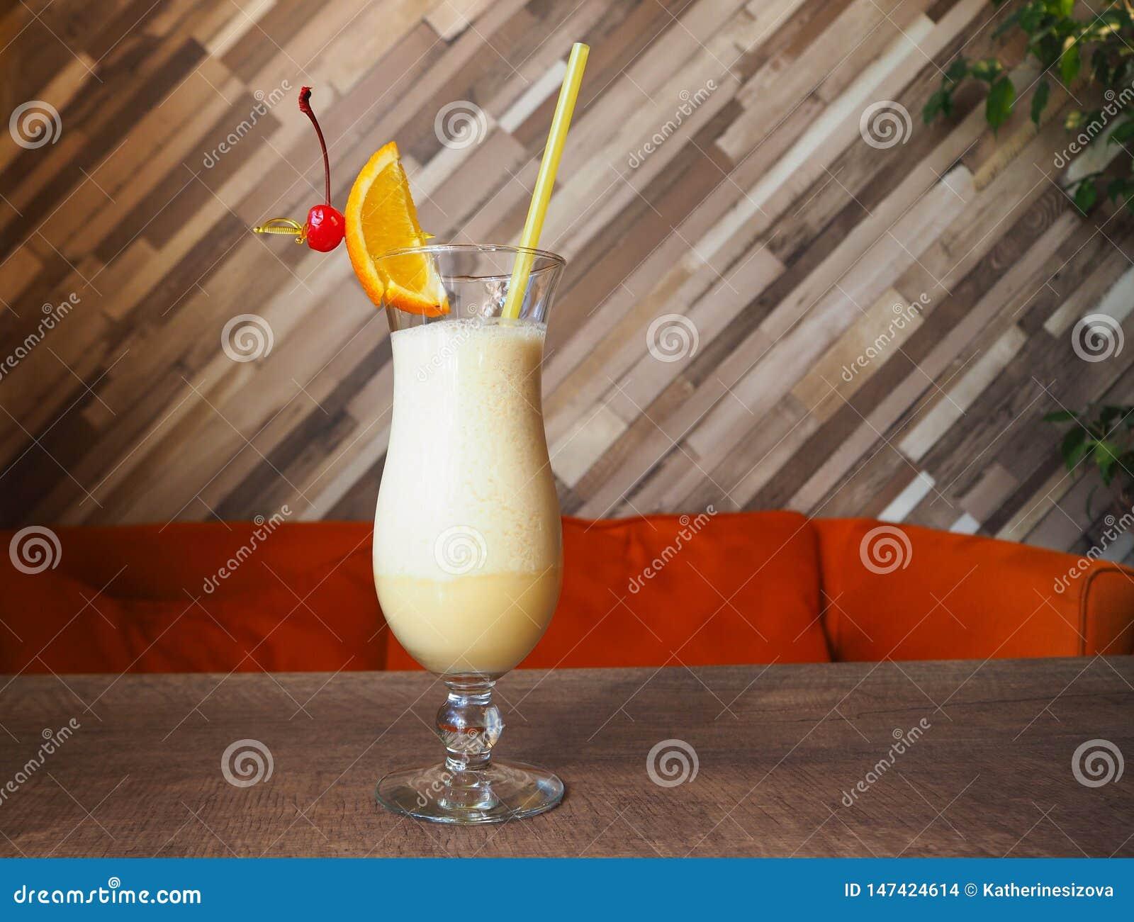 Cocktail branco e amarelo doce com espuma do leite e com parte de laranja e de cereja