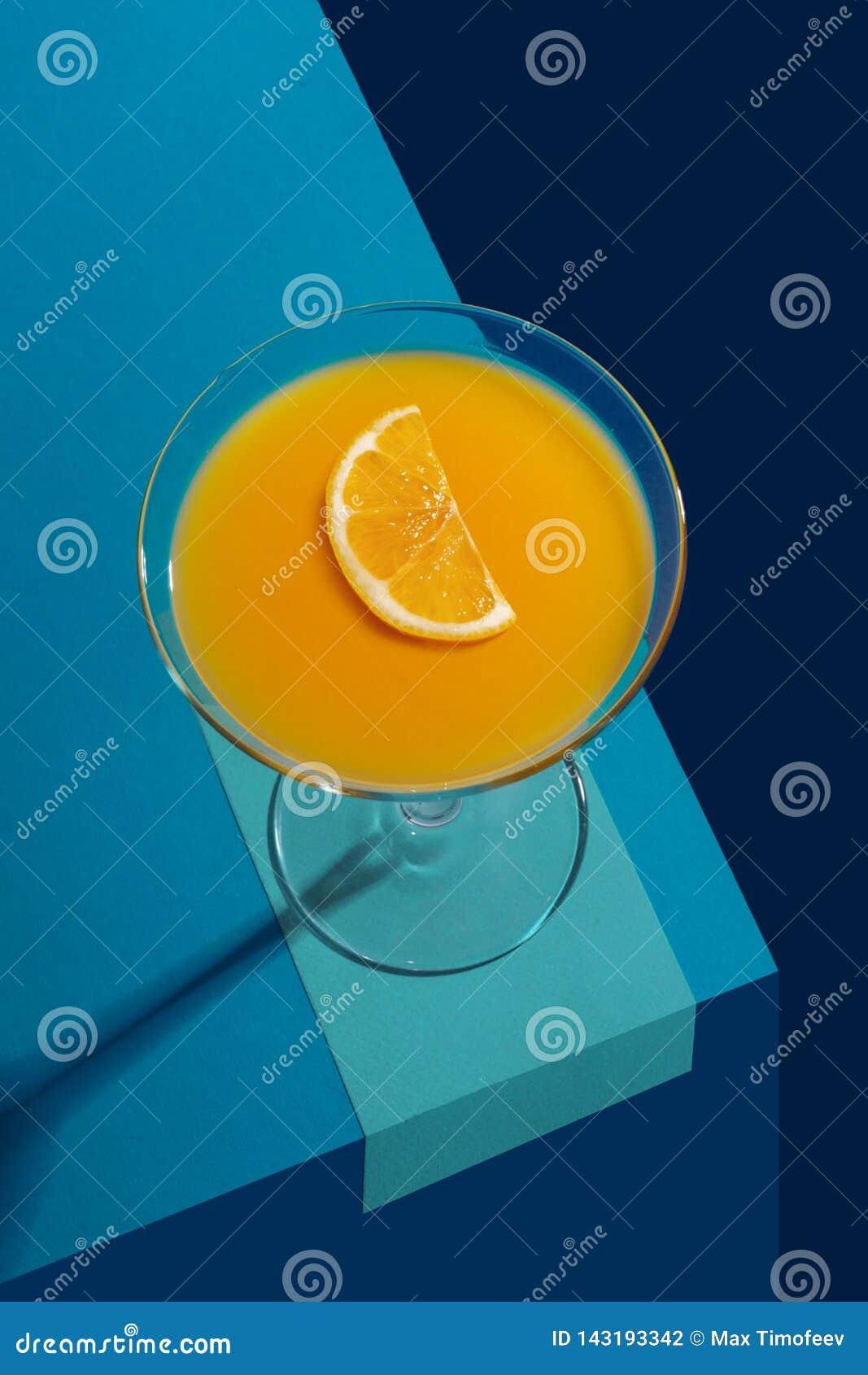 Cocktail con il limone in un becher di vetro su un fondo astratto blu Concetto creativo