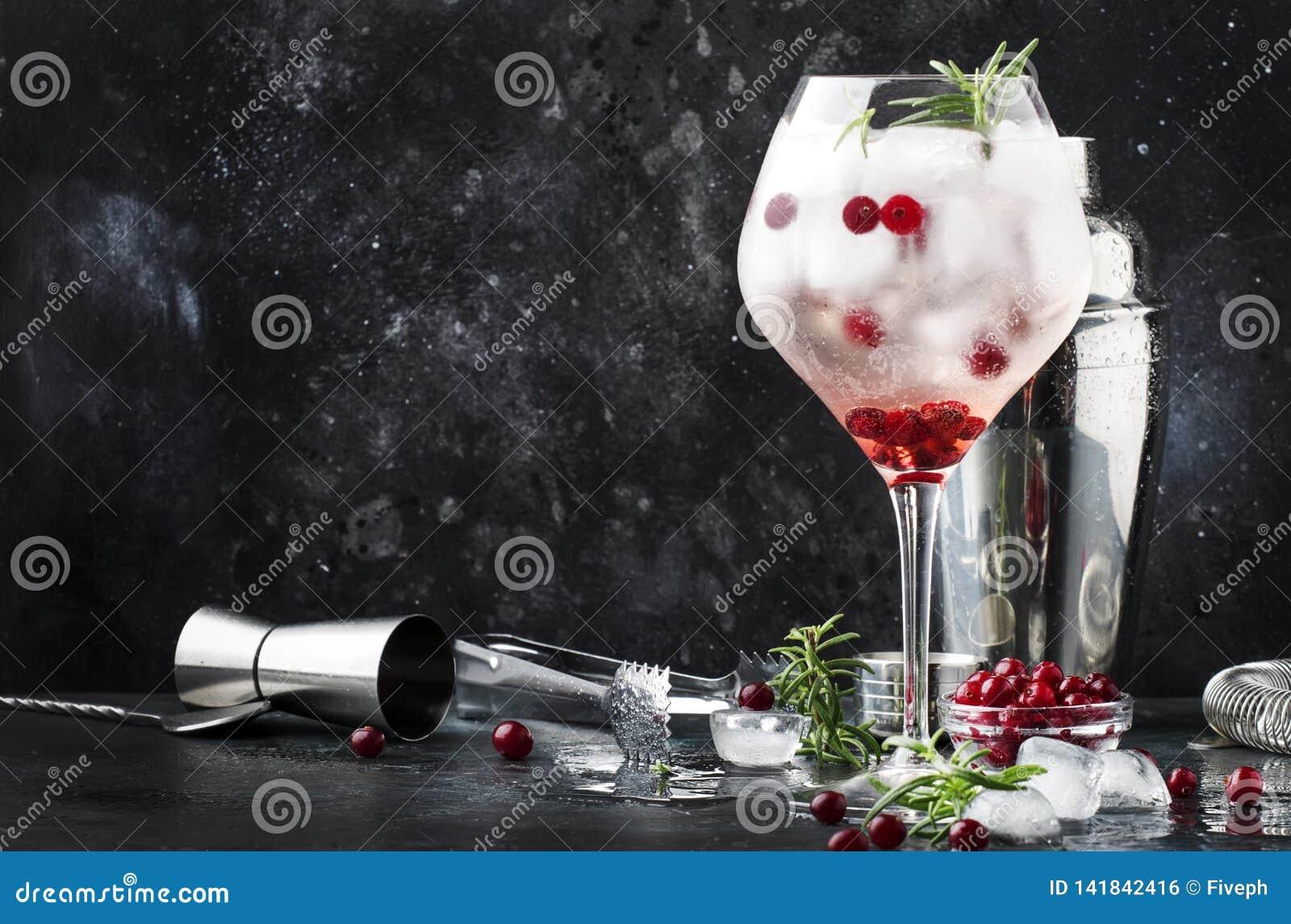 Cocktail de canneberge avec de la glace, le romarin et les baies en grand verre de vin, outils de barre, fond de compteur de barr
