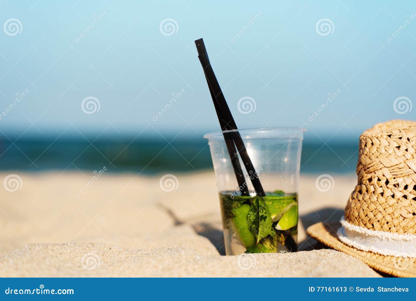 Cocktail de Mojito sur la plage et le chapeau de paille Fond brouillé de plage avec l espace de copie Sun, brume du soleil, éclat