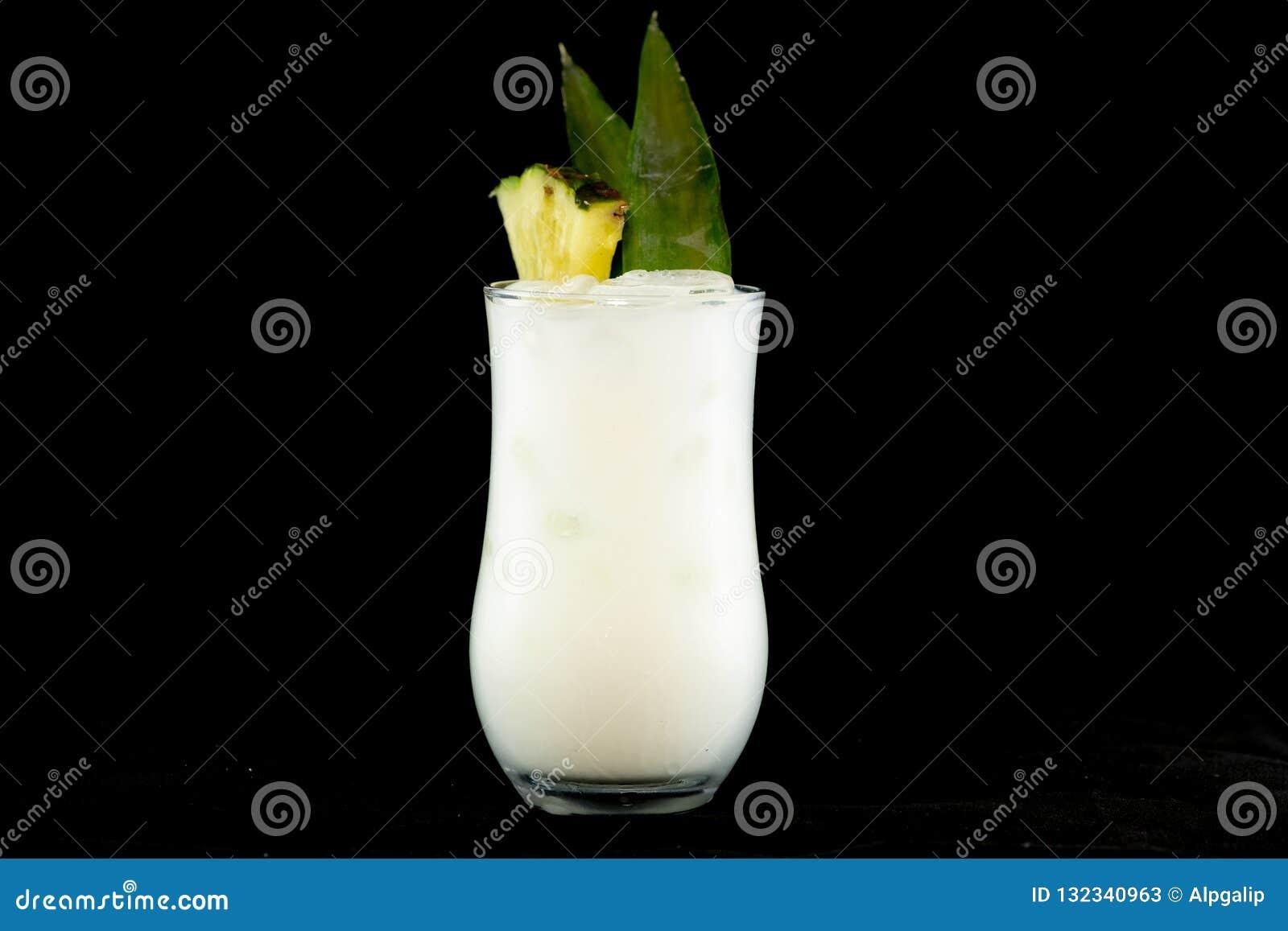 Cocktail di Pina Colada con il succo di ananas, il rum bianco e la crema della noce di cocco decorati con la frutta e la foglia d