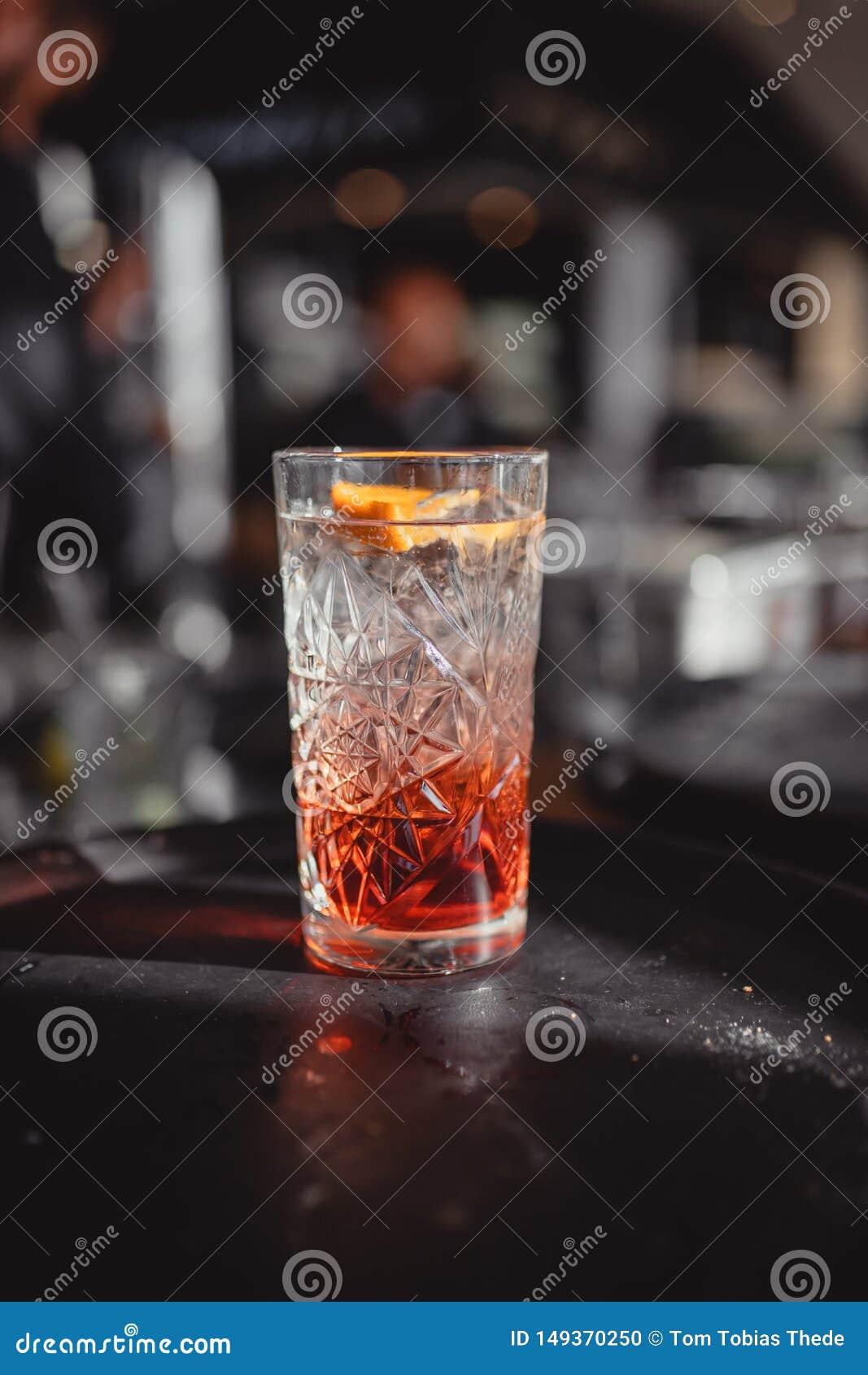 Cocktail em uma barra do cocktail com alaranjado e o vermelho