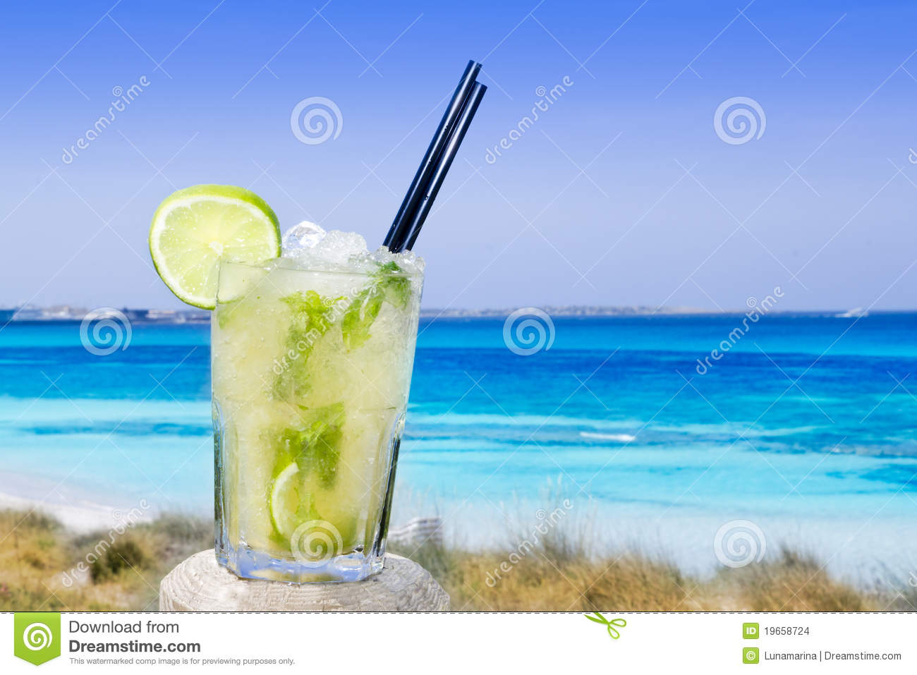 Cocktail mojito ice lemon straws in tropical beach balearic Islands.