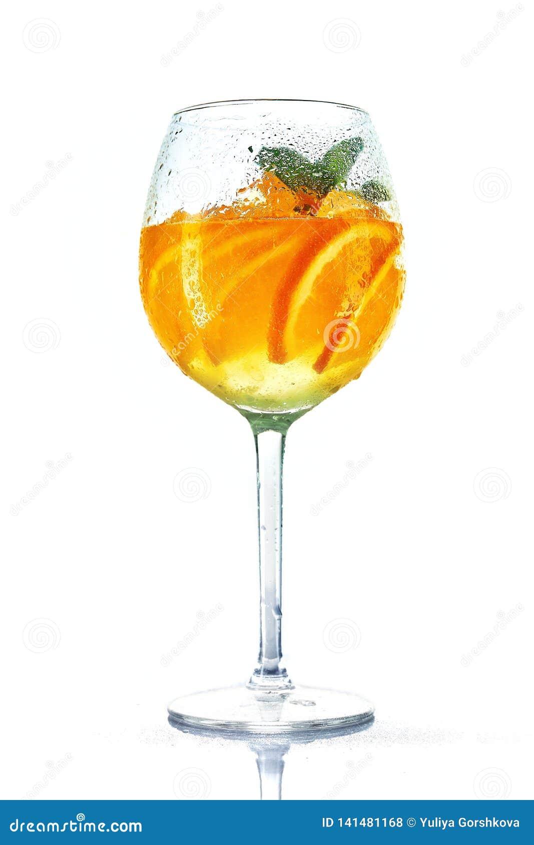 Cocktail orange en verre de vin avec la menthe sur le fond blanc Verre de Misted