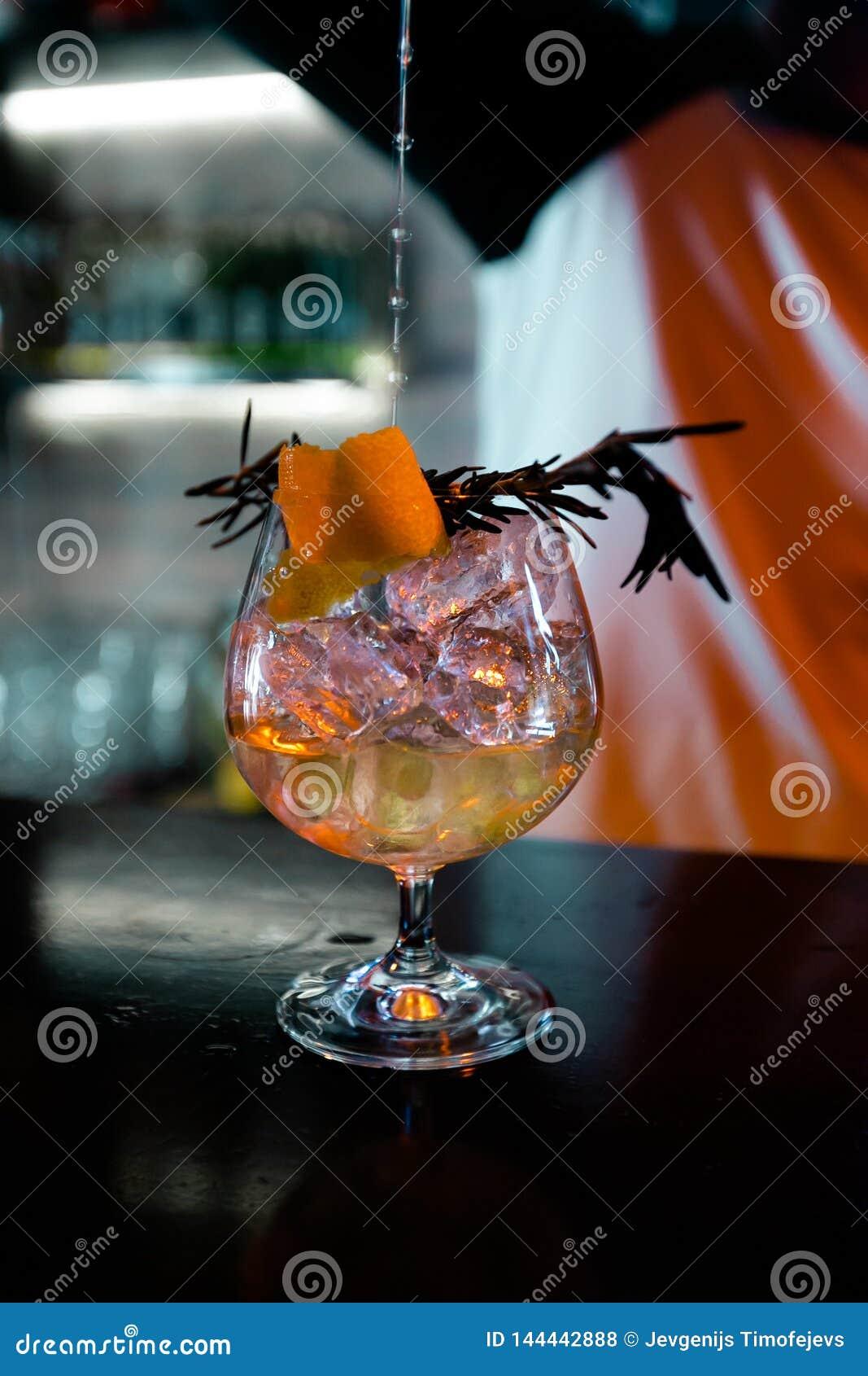 Cocktail pelo empregado de bar em um clube noturno - as habilidades do barman são mostradas