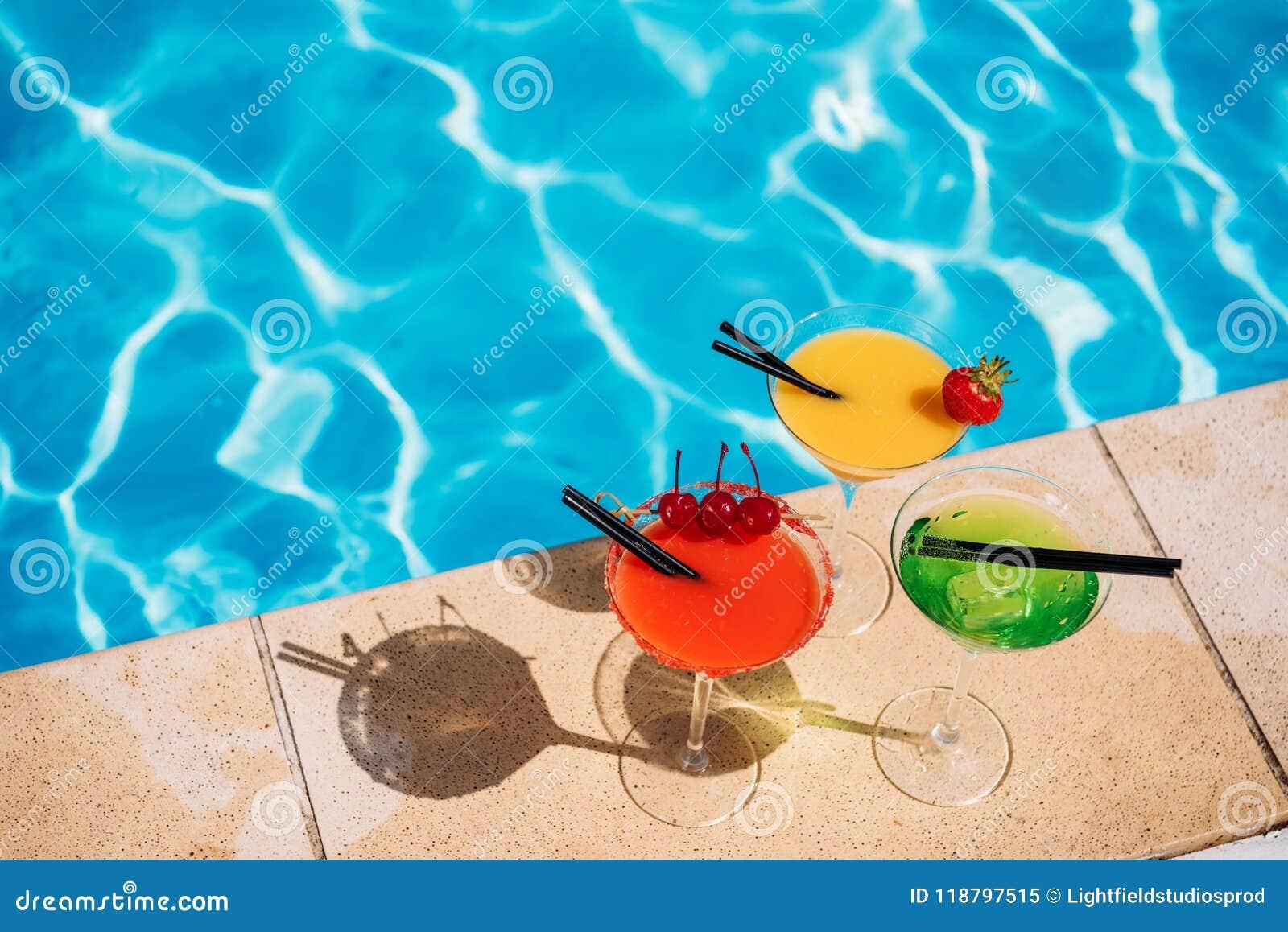 Cocktail tropicale variopinto con le bacche sul bordo della piscina