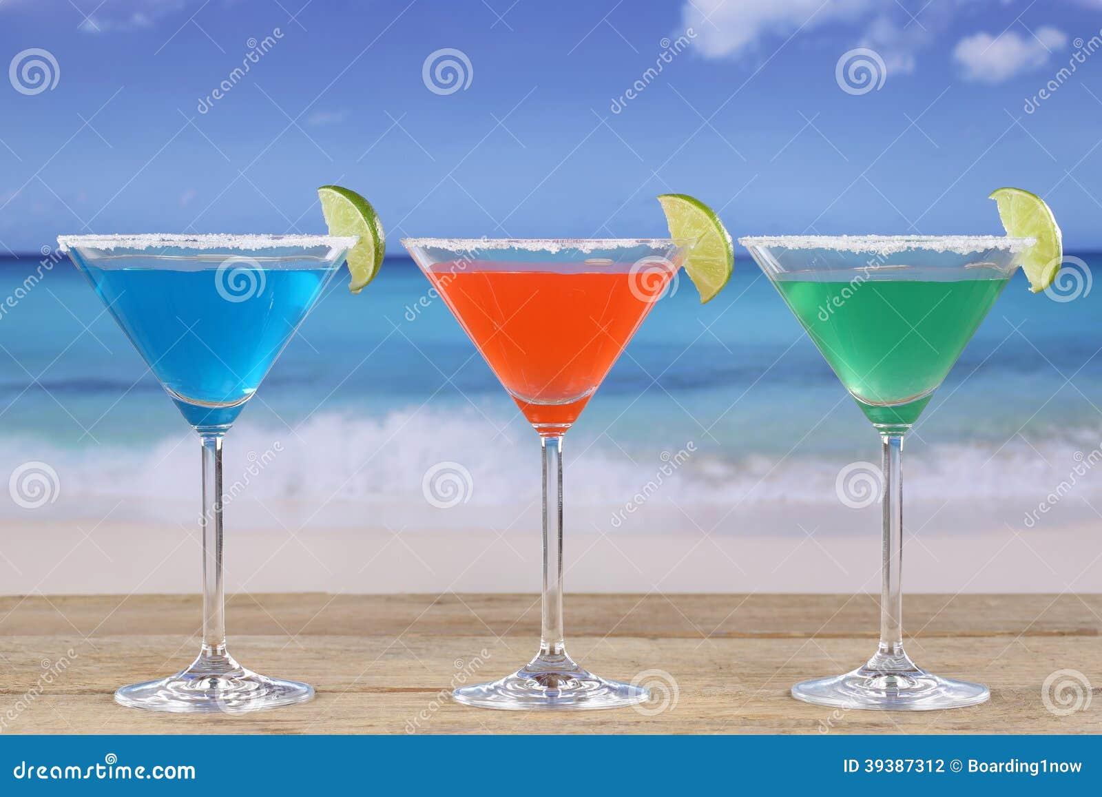 Cocktail variopinti in vetri di Martini sulla spiaggia
