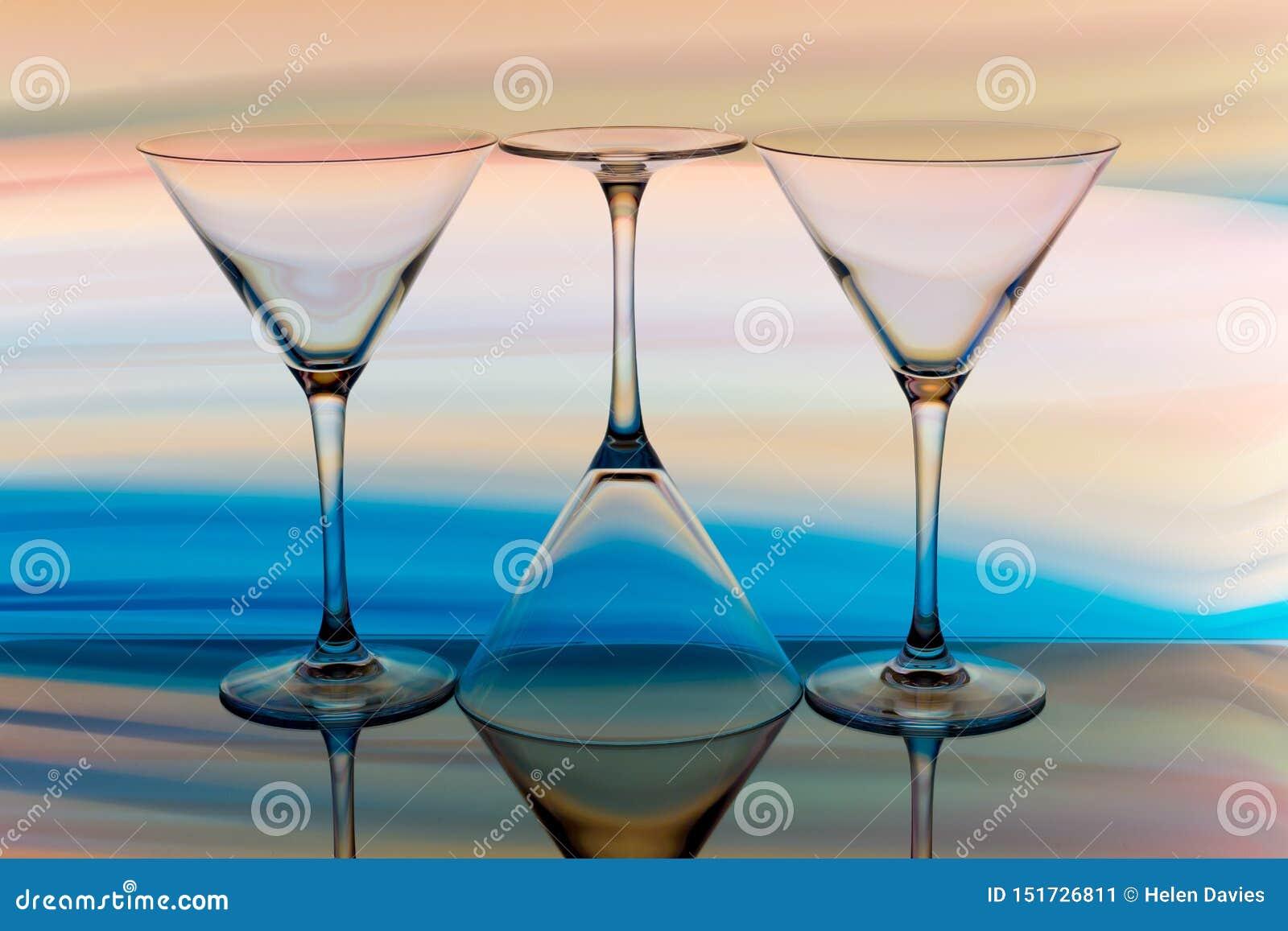 Cocktail/vidro de martini com um arco-íris da cor atrás