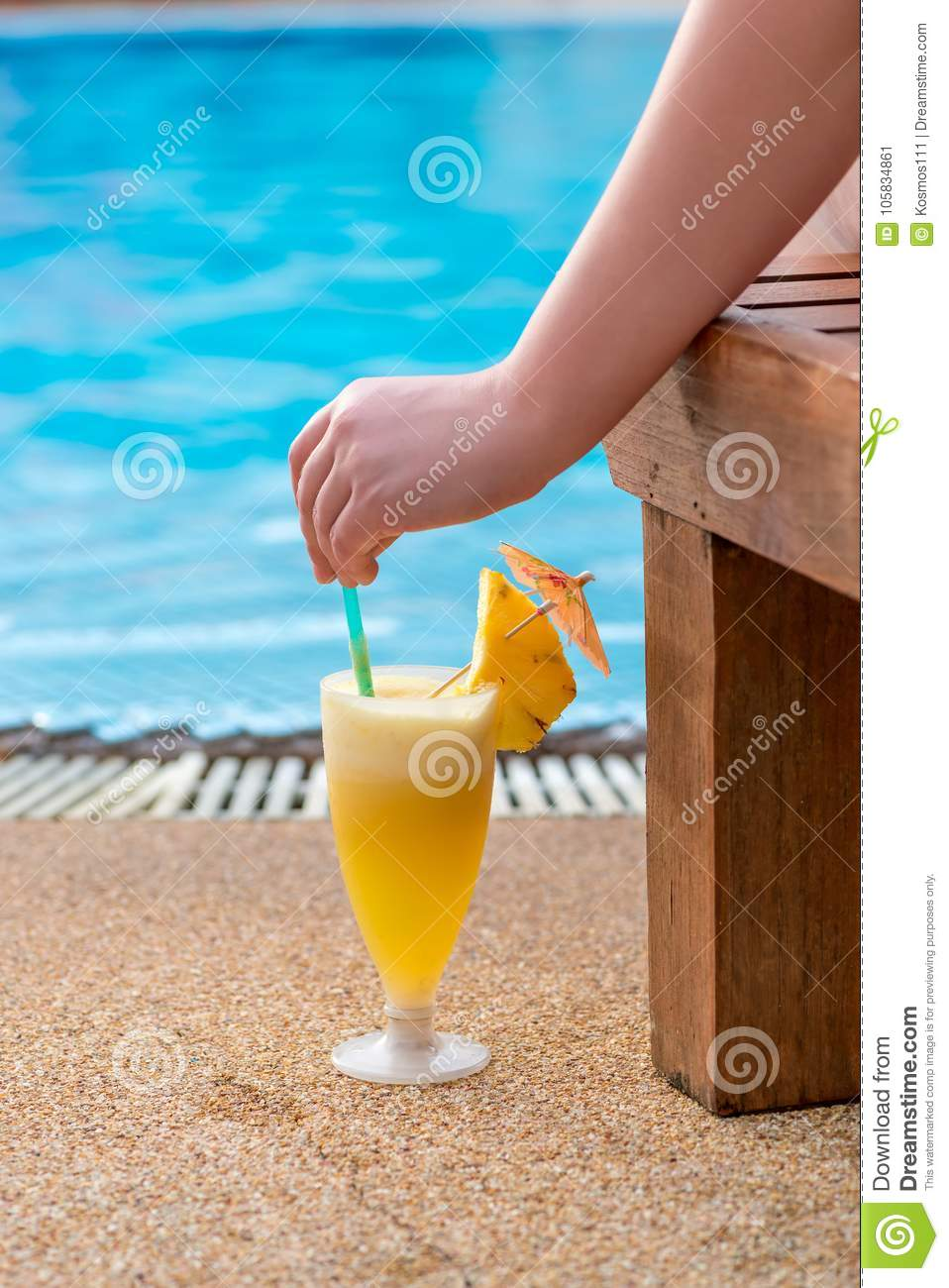 Cocktail, woman`s hand and view of the pool
