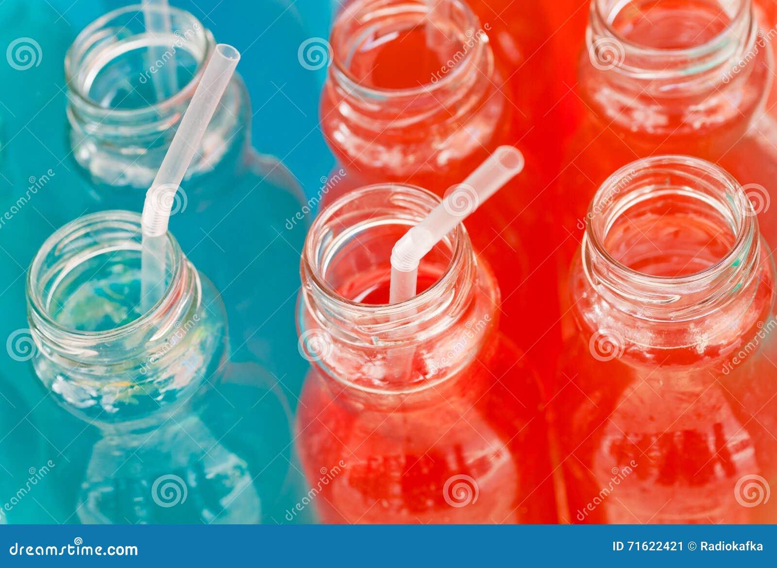 Cocktailrohre in den Krügen mit bunten Energied-clips mit den Sirup-, Roten und Blauenfarben