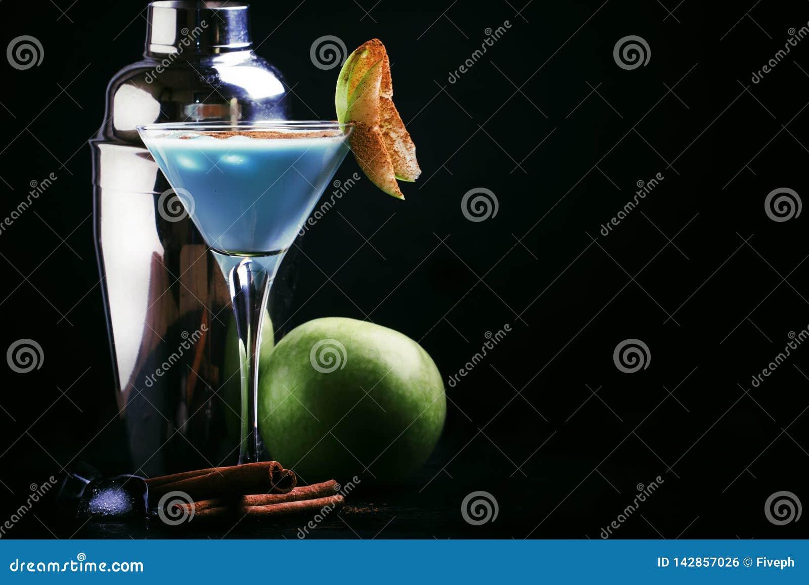 Cocktails bleus avec la liqueur, la crème et la pomme verte, outils de barre sur un fond noir de compteur de barre, l espace de c