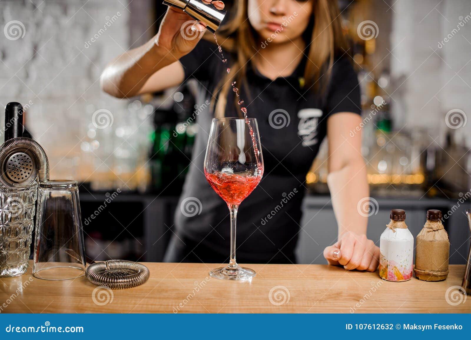 Cocktails de mélange de barmaid au compteur de barre utilisant l équipement de barre
