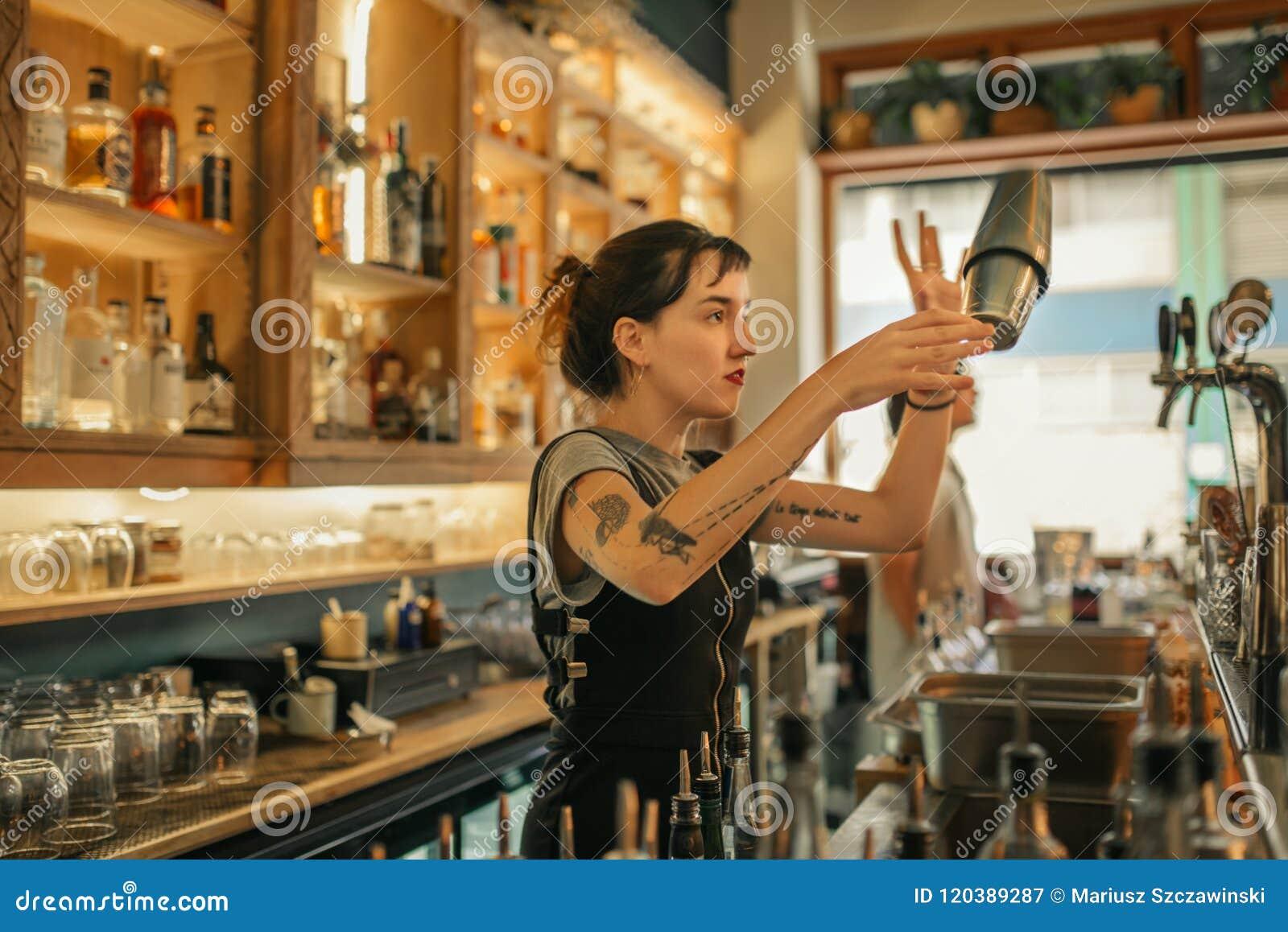 Cocktails de mélange de jeune barman féminin derrière un compteur de barre