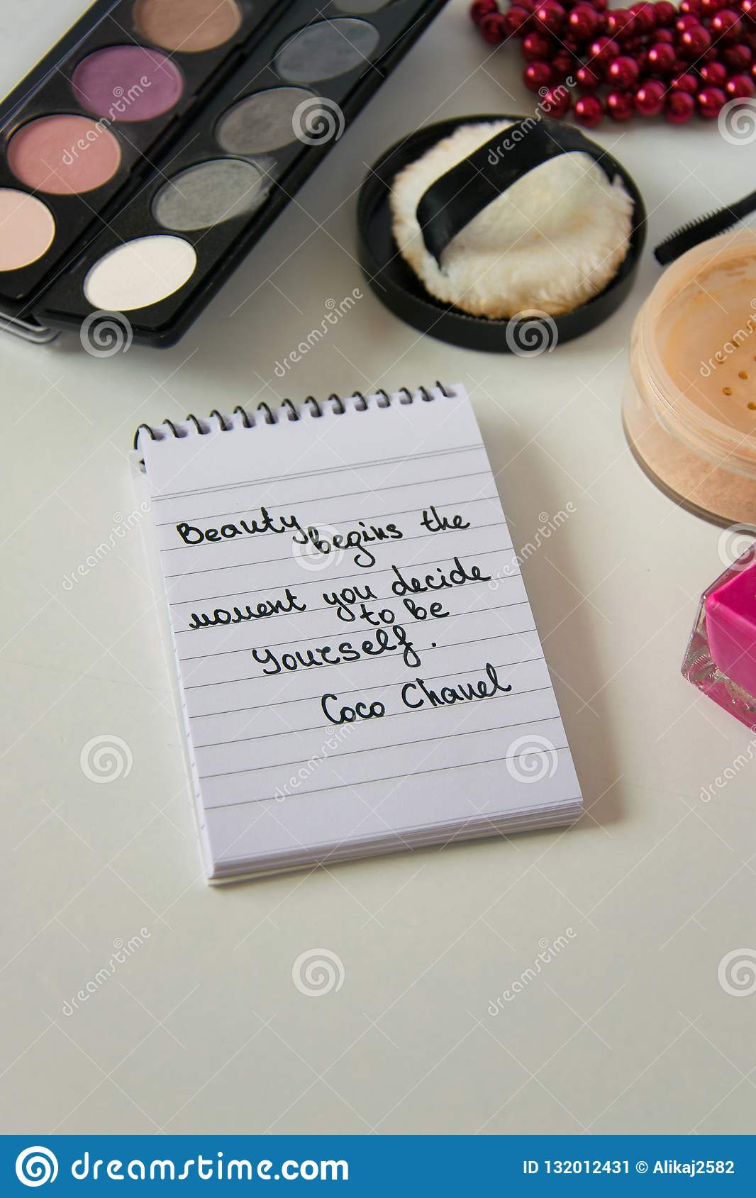 Coco Chanel quotes written on a block note, pearl accessories and make up on white background