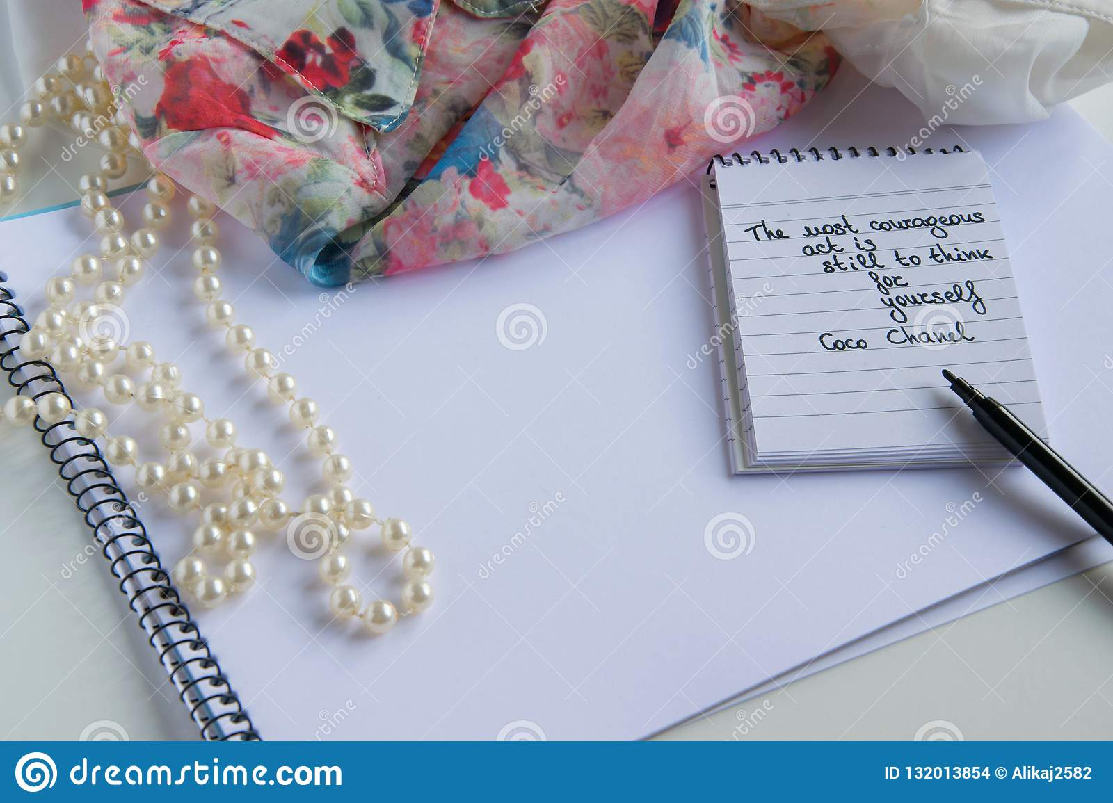 Coco Chanel quotes written on a block note, pearl accessories and an silky flower shirt