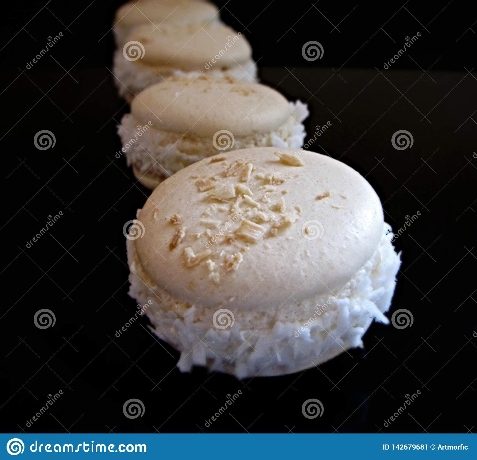 Coconut french macarons on black background