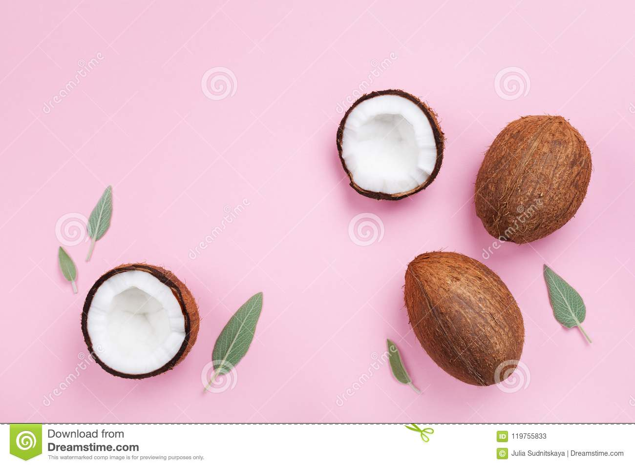 Coconut fruit whole and half on pink pastel background top view. Flat lay style.