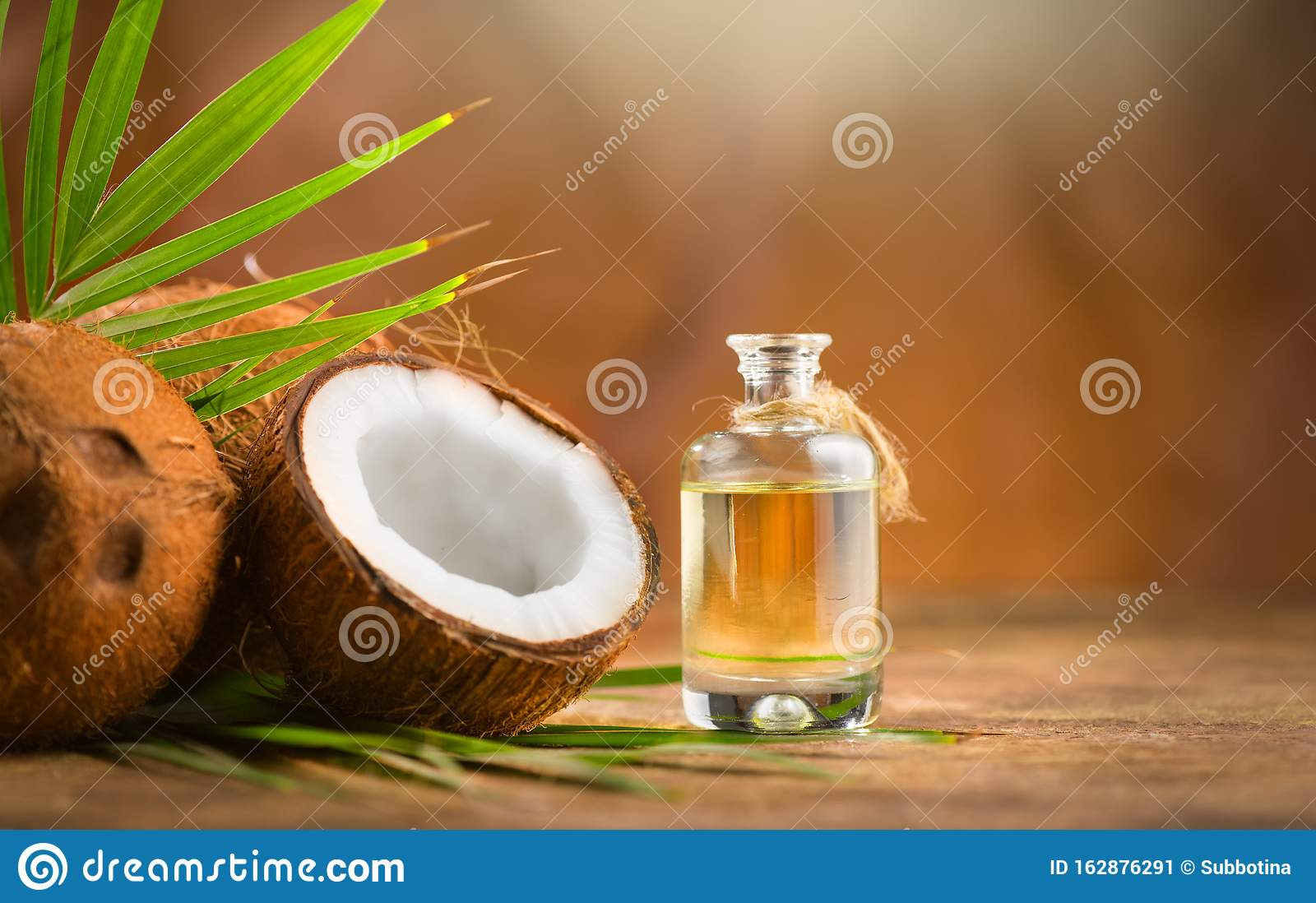 Coconut palm oil in a bottle with coconuts and green palm tree leaf on brown background. Coco nut closeup. Healthy Food, skin care