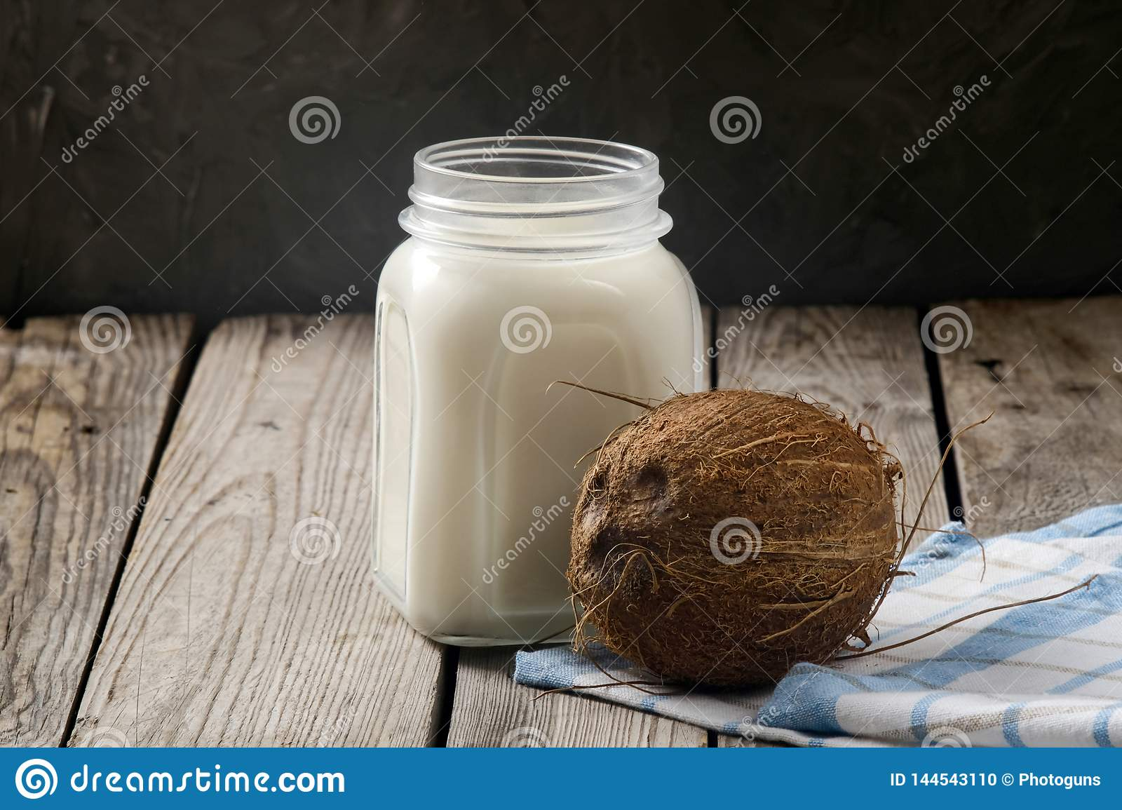 Coconut vegan milk non dairy in jar and coconut on dark wooden table. Fresh organic coconut milk or water, close up