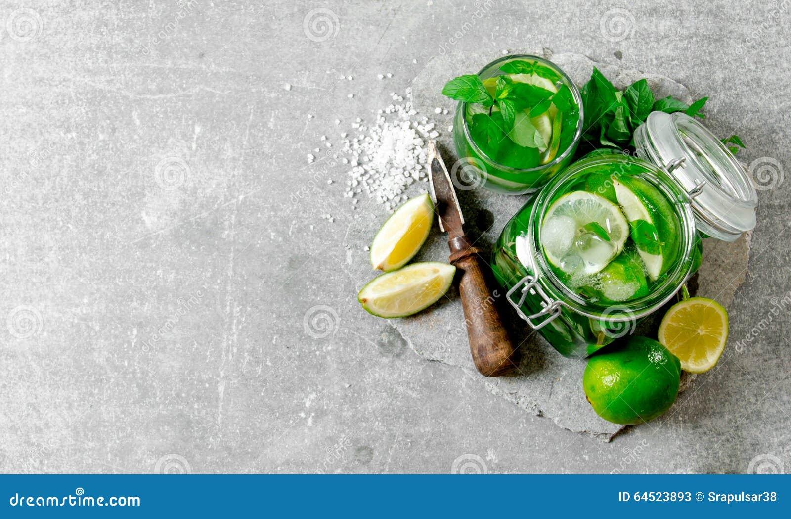 Coctail i kruset - mintkaramellsidor, is, rom och limefrukt på en stengrund med en kniv för citrus och socker