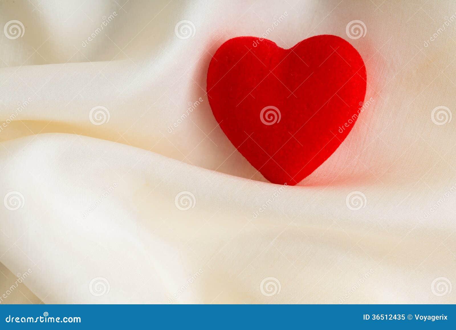 Coeur décoratif en bois rouge sur le fond en soie blanc.