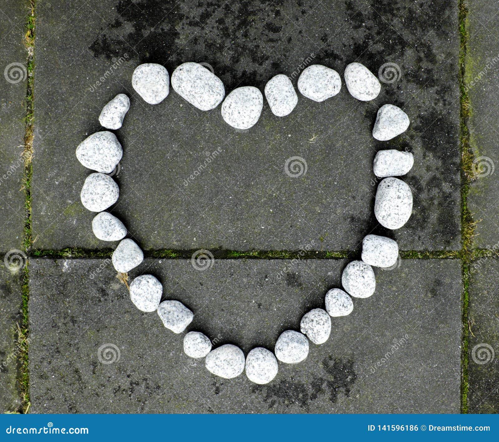 Coeur de pierre fait de petites pierres blanches sur le fond en pierre foncé