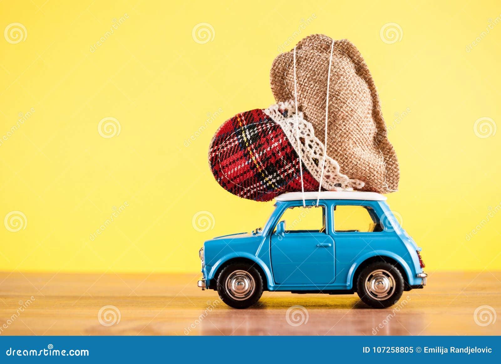 Coeur de transport de voiture de jouet sur le fond jaune