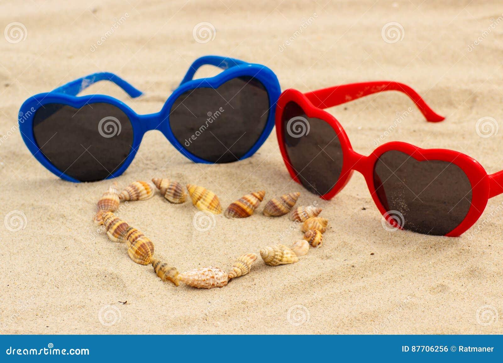 Coeur des coquilles et des lunettes de soleil sur le sable à la plage