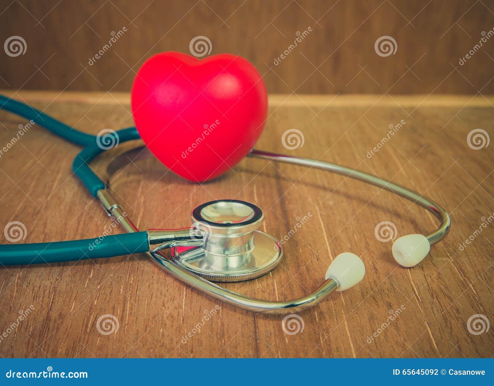 Coeur et stéthoscope rouges sur le fond en bois