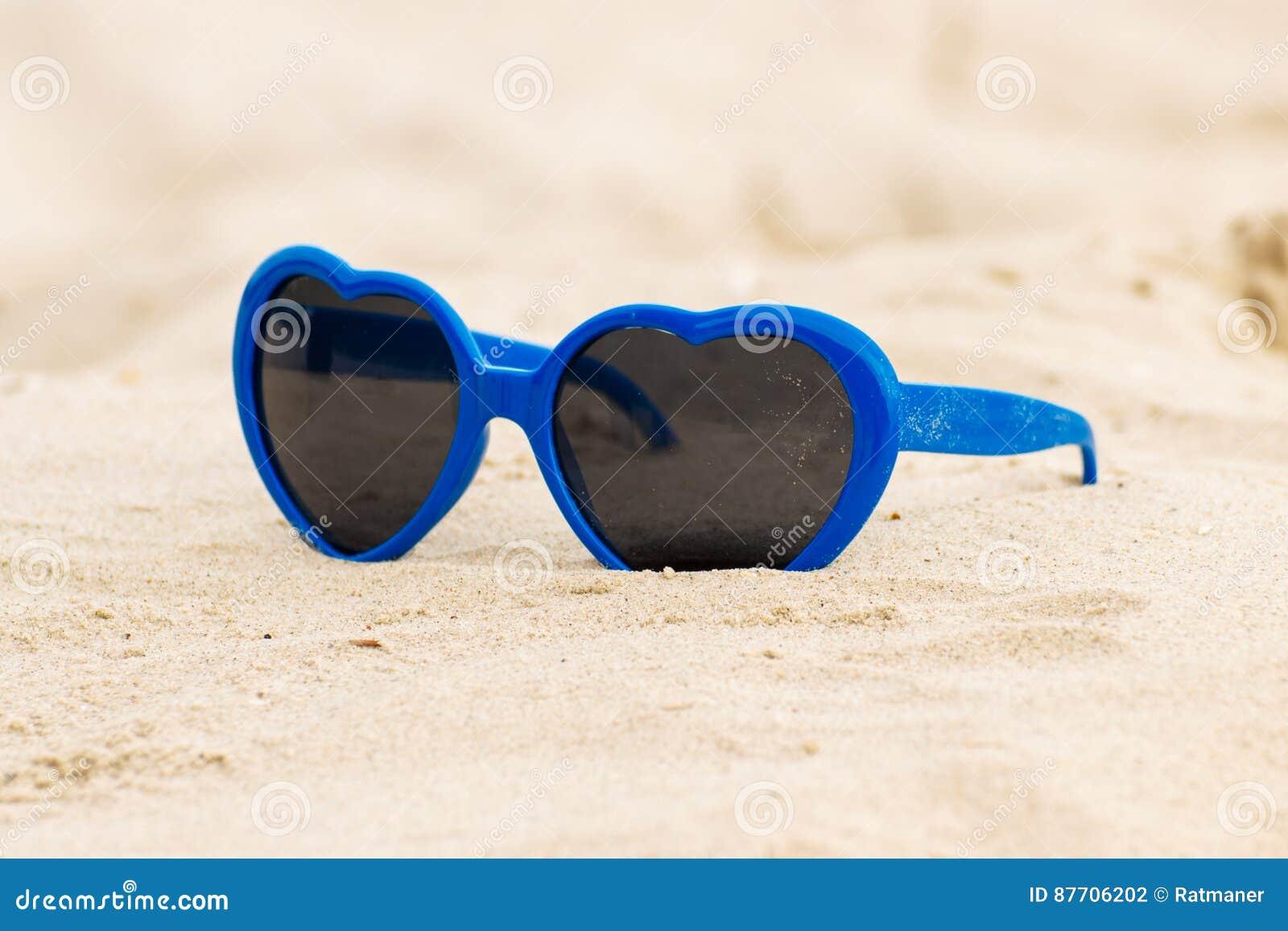 Coeur formé par lunettes de soleil bleues sur le sable