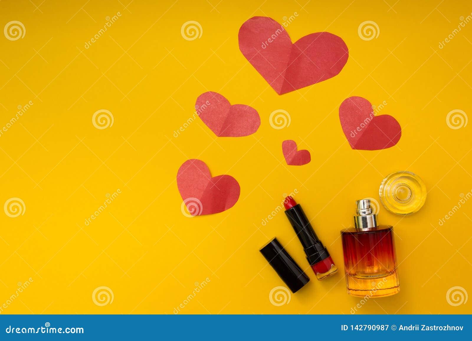Coeur, rouge à lèvres et parfum sur un fond jaune