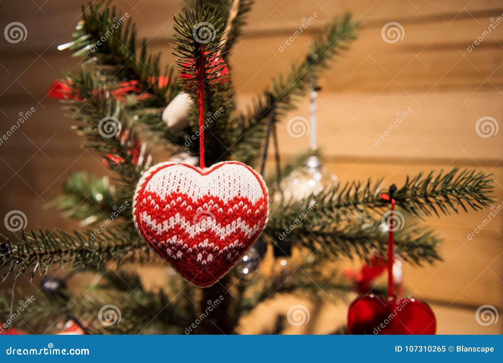 Coeur rouge accrochant sur l arbre de Noël