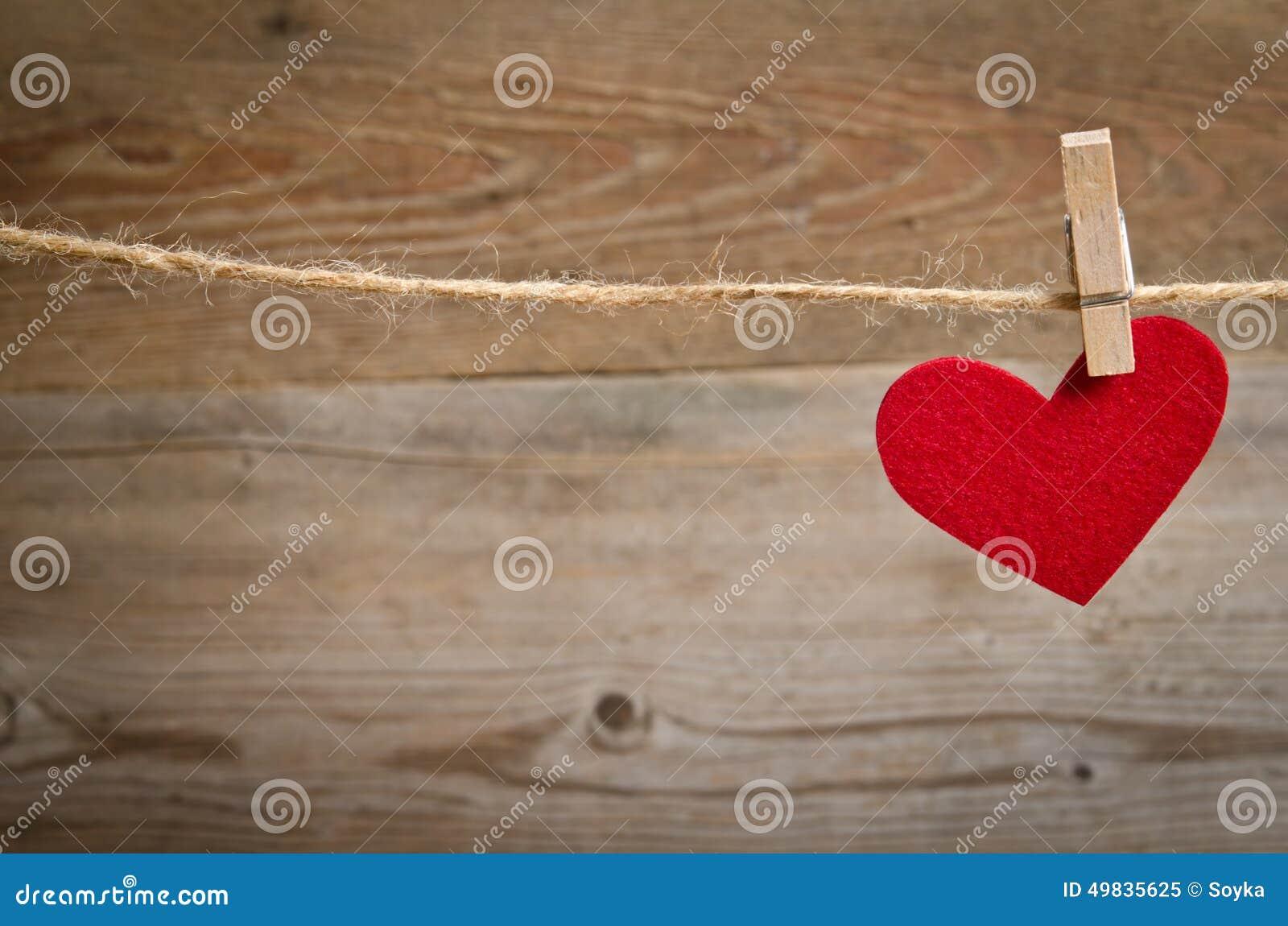 Coeur rouge de tissu accrochant sur la corde à linge