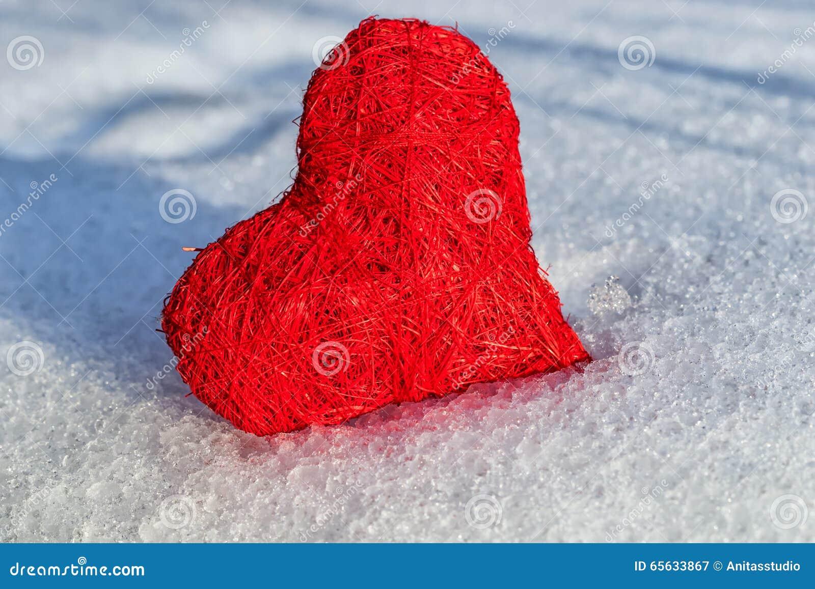 Coeur rouge de valentines sur la neige humide de glace