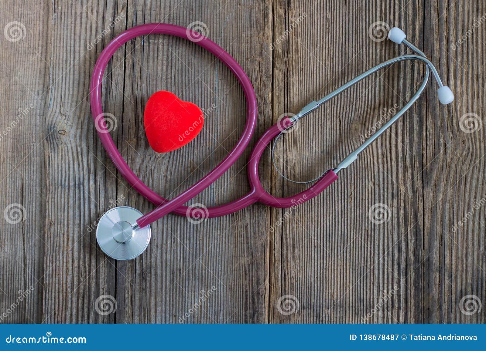 Coeur rouge et un stéthoscope sur le vieux bureau en bois horizontal