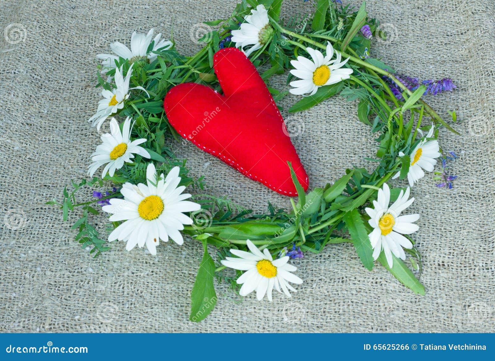 Coeur rouge fait en tissu de feutre et une guirlande des fleurs de champ