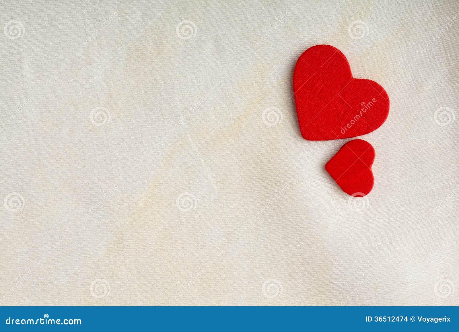 Coeurs décoratifs en bois rouges sur le fond blanc de tissu.