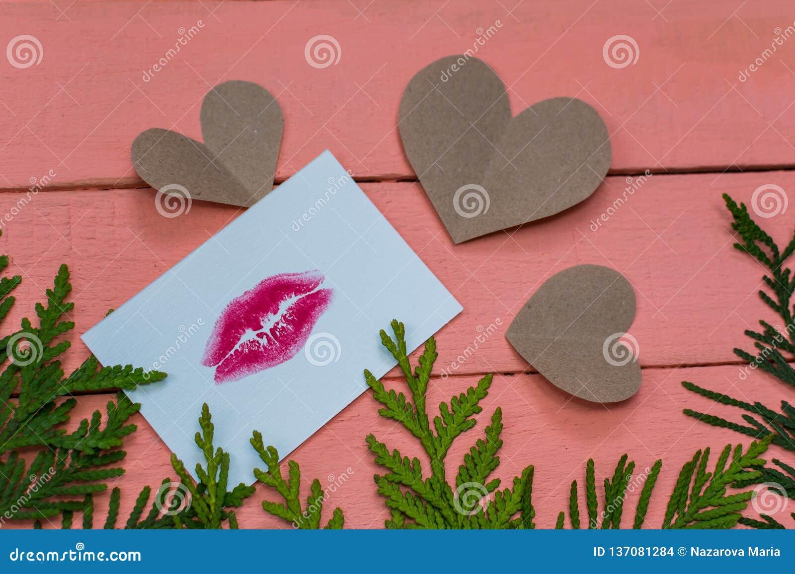 Coeurs et carte avec la copie de lèvre sur le fond en bois rose