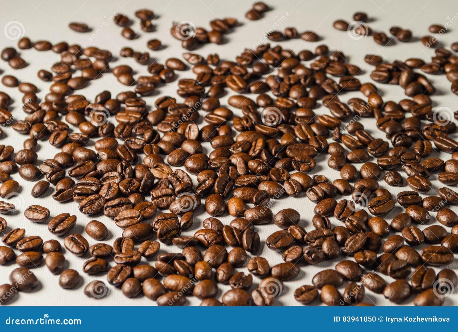 Coffebeans στο ουδέτερο γκρίζο υπόβαθρο σκοτεινό roast καφέ