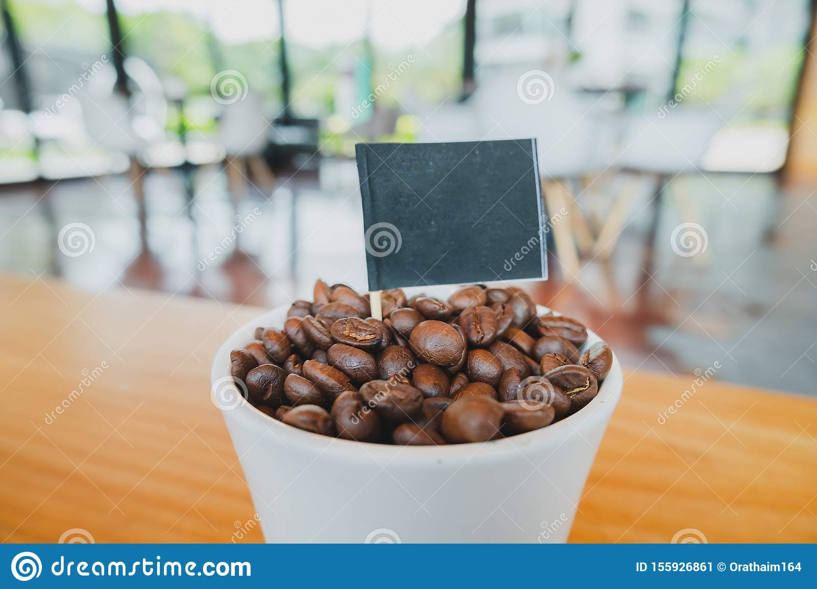 Coffee bean in white ceramic cup and black flag with brown wooden background