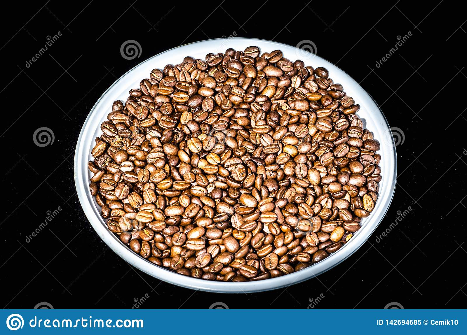 Coffee beans on a round plate close up. Isolated on black background