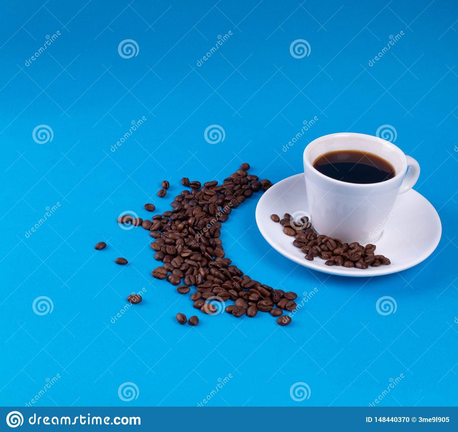 Coffee beans are scattered in a crescent next to white china on a blue background