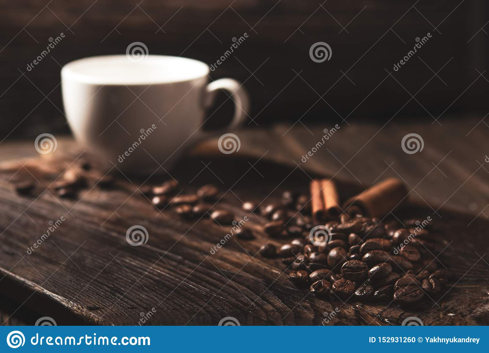 Coffee beans and white mug on wooden dark background