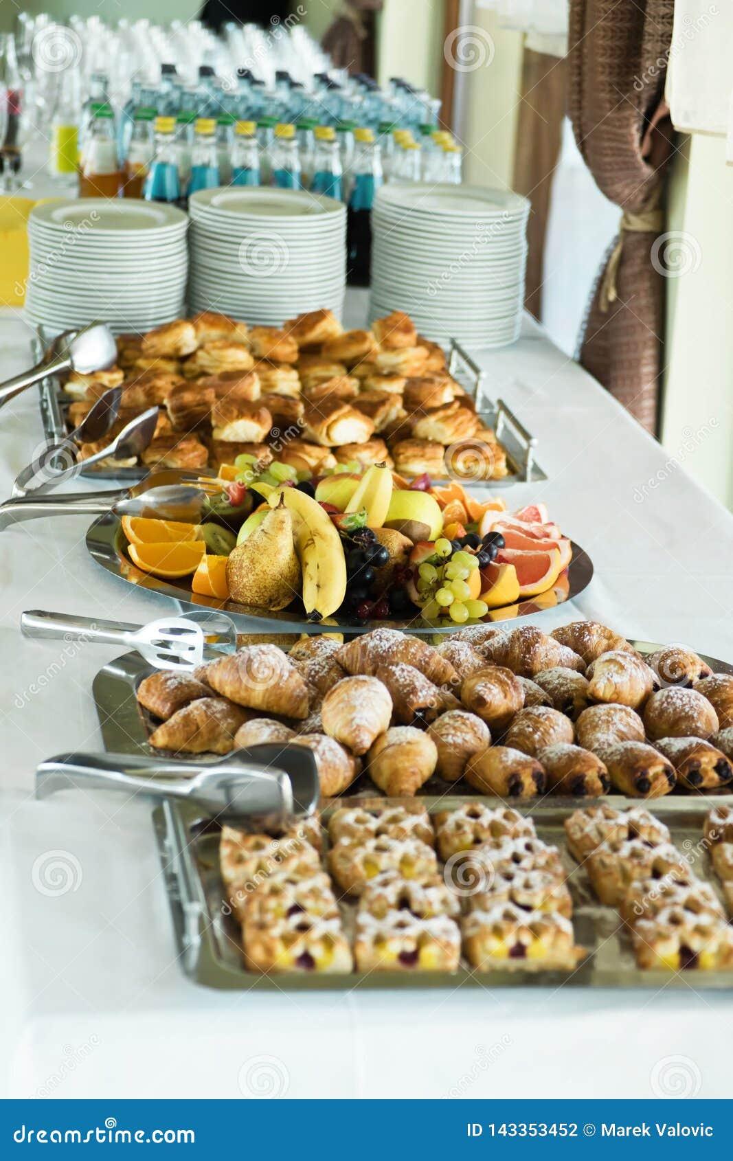 Coffee break table on seminar cakes, fruit, drinks